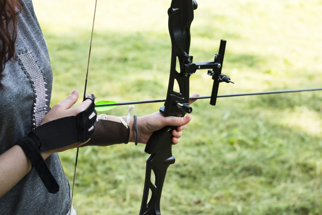 Female archer holding bow and arrow, getting ready to aim